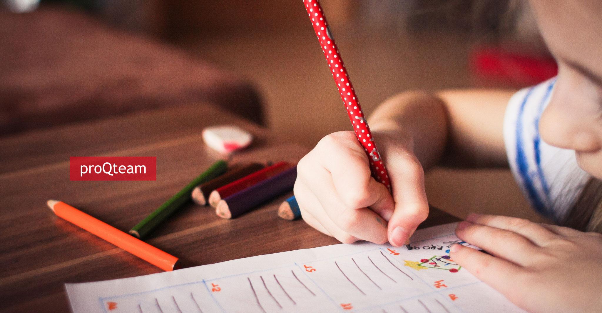 Kind malt mit Stiften auf Papier